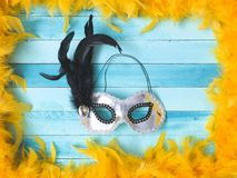 Blue carnival background with yellow feathers stock photos
