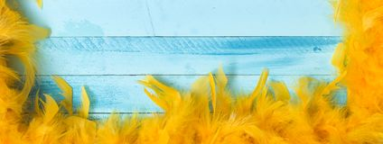 Blue carnival background with yellow feathers royalty free stock photo