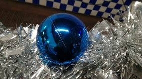 Big blue Christmas ball. A beautiful blue Christmas ball in the midst of silver decorations Royalty Free Stock Photography