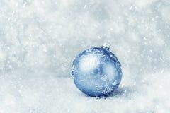 Blue Christmas ball on the snow. Beautiful Blue Christmas ball on the snowy background, copy space Stock Photo