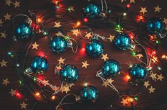 Beautiful blue christmas balls, golden star confetti and a glowing garland on the wooden table top view. Festive toned background royalty free stock photography