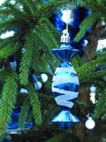 Beautiful blue Christmas decoration hanging on fir tree branch. Nice blue with white ornaments decoration hanging on fir tree branch before Christmas and new Stock Photography