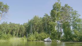 Beautiful blue clear water on the shore of the lake. Forest landscape at coast mirrored in water.  stock video footage