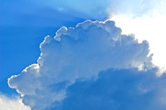 Beautiful blue clouds with the sun hiding Royalty Free Stock Photo