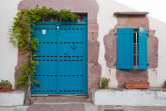 The beautiful blue doors in Basque Country. The doors andthe  window with wisteria Royalty Free Stock Photography
