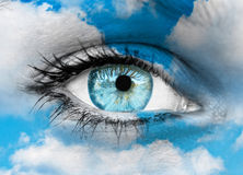 Beautiful blue eye against blue clouds - Spiritual concept. This image represents Beautiful blue eye against blue clouds - Spiritual concept Royalty Free Stock Image