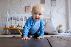 Beautiful blue-eyed baby crawling on the wooden floor.  stock photos