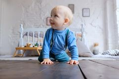 Beautiful blue-eyed baby crawling on the wooden floor.  royalty free stock photography