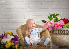 Beautiful blue-eyed baby. With flowers royalty free stock image