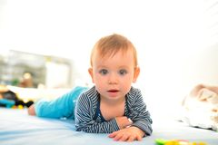 Crawling baby kid. Beautiful blue eyed baby kid crawling in bed stock images