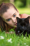 Beautiful Blue Eyed Female Girl Teenager With Black Cat. Beautiful female teenager girl young woman with blue eyes, laying down outside on grass with a black cat Stock Photos