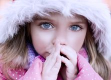 Beautiful blue-eyed girl who warms frozen hands. Pretty blue-eyed girl who warms his hands frozen in a cold day Royalty Free Stock Images