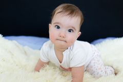 Beautiful blue eyed little baby on the bed.  stock photo
