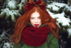Beautiful blue eyed red haired smiling girl posing in front of snow covered firtrees. Fairytale concept stock photography