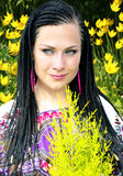Beautiful blue-eyed woman with the african pigtails. On a background yellow tulips with young thuja in hands Royalty Free Stock Image