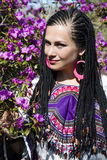 Beautiful blue-eyed woman with the african pigtails. Among the branches of flowering magnolia Stock Photo