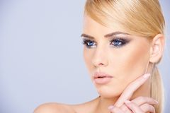 Beautiful blue-eyed woman wearing makeup. Beautiful blue-eyed blond woman wearing dark eye makeup looking at the camera close up head portrait Royalty Free Stock Photos