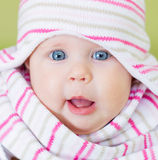Beautiful blue eyes baby. Cute Smiling Baby Girl Portrait With Big Blue Eyes in Knit Hat and Scarf Stock Photo
