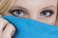 Beautiful blue eyes blue scarf. A beautiful woman with bright blue eyes holds up a blue scarf Royalty Free Stock Image