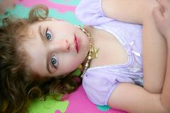 Beautiful blue eyes little girl lying on floor. Beautiful blue eyes little girl liying on the floor Stock Images