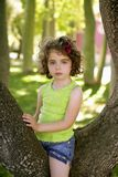 Beautiful blue eyes little girl in the park tree Royalty Free Stock Photography