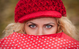 Beautiful blue eyes over colorful umbrella. Attractive blonde girl with red cap looking over red umbrella outdoor shoo. T. Attractive young woman in a autumn Stock Images