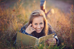 Beautiful blue eyes woman reading a book outdoor Stock Image