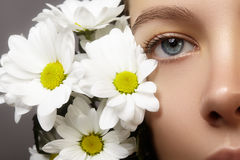 Beautiful blue female eye with white spring flower. Clean skin, fashion naturel make-up. Good vision, healthcare. Close-up macro of beautiful female eye with royalty free stock photography