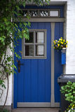 Beautiful blue front door with windows in a white painted brick Stock Photography