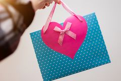 Beautiful blue gift bag with pink heart on white background on girl`s hand. Valentine`s Day stock image