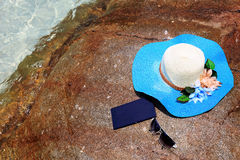 Beautiful blue hat , mobile and sunglasses on the stone Royalty Free Stock Image
