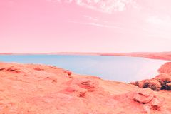 Beautiful blue lake on the background of coral coast and pink sky stock image