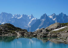 Beautiful blue lake in European alps, with Mont Blanc in the background. Beautiful mountain scenery, on the Tour of Mont Blanc, France Royalty Free Stock Images