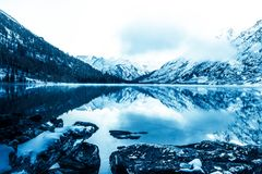 Beautiful blue lake in the mountains. Flat mirror surface of the water under the clouds. stock photography