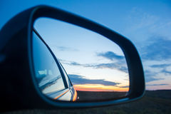 Beautiful blue landscape sunset reflect in mirror of car Royalty Free Stock Images
