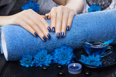 Beautiful blue manicure with chrysanthemum and towel on the black wooden table. spa. Beautiful blue manicure with oil and candles, chrysanthemum and towel on the royalty free stock photo