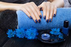 Beautiful blue manicure with chrysanthemum and towel on the black wooden table. spa Stock Image