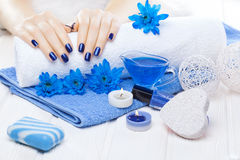 Beautiful blue manicure with chrysanthemum and towel on the white wooden table. spa Royalty Free Stock Photos