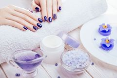 Beautiful blue manicure with spa essentials. On wooden background Royalty Free Stock Photos
