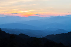 Beautiful blue mountain layers in the fog during sunset Stock Images