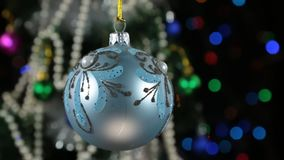 Beautiful blue New Year and Christmas decoration ball swinging on rope. Against a background of a rotating Christmas tree and a flashing garland stock video