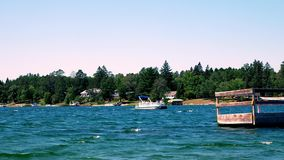 Beautiful blue northern Minnesota lake with wooded shoreline and homes on a sunny day with a pontoon approaching. Beautiful blue northern Minnesota lake with stock video footage