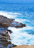 Beautiful blue ocean water hitting against rocky edge Stock Photo