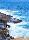 Beautiful blue ocean water hitting against rocky edge Stock Photo