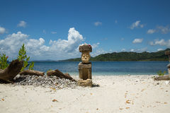 Beautiful blue ocean and white sand beach and stone man carving. Royalty Free Stock Photography