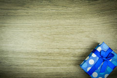 Beautiful blue a present with blue beads on a wooden background.  Royalty Free Stock Images