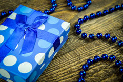 Beautiful blue a present with blue beads on a wooden background.  Stock Photography