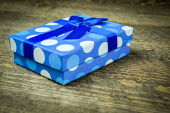 Beautiful blue a present with blue beads on a wooden background.  Stock Photos