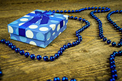 Beautiful blue a present with blue beads on a wooden background.  Stock Image