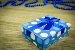 Beautiful blue a present with blue beads on a wooden background.  Royalty Free Stock Photos